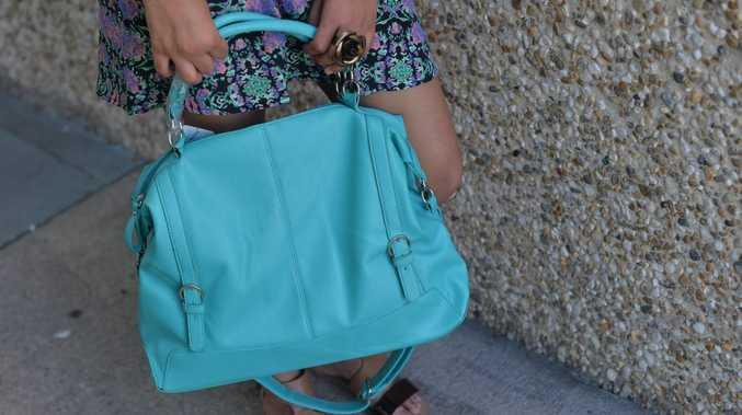 A thief has stolen a Good Samaritan's handbag while she comforted an elderly woman involved in a serious crash.