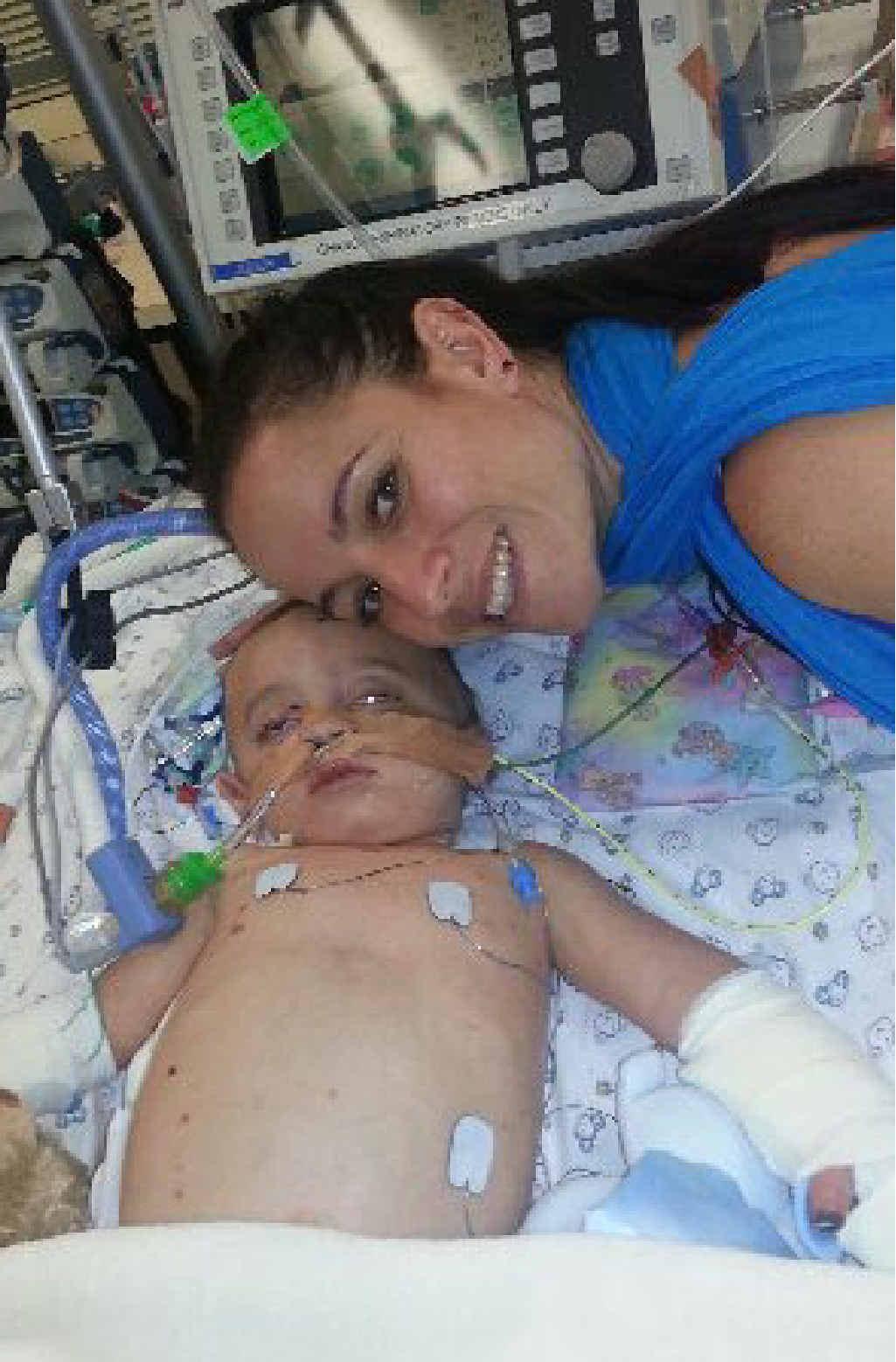 LONG JOURNEY: Sarah Smith comforts her son Finn in Royal Brisbane Hospital.