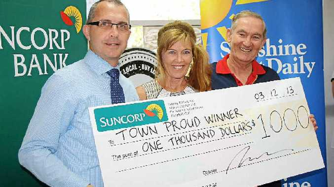 TOWN PROUD: Suncorp Bank regional general manager James McLellan presents a $1000 cheque to Carmel and Michael Parkinson of David Low Way News.