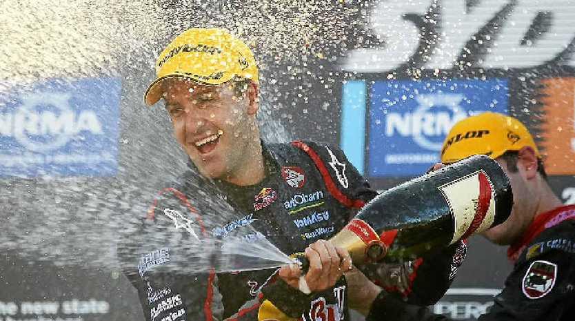 WINNER: Jamie Whincup celebrates winning the V8s championship.