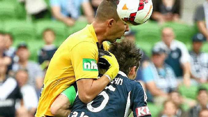 OUCH: Mark Birighitti collides with Victory captain Mark Milligan.