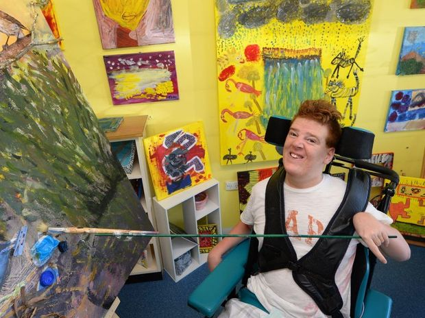 David Whittaker has not let Cerebral Palsy stop him from putting paintbrush to canvas to produce his art. David's paintings can soon be seen at the Multicap Exhibition. Photo: Chris Ison / The Morning Bulletin