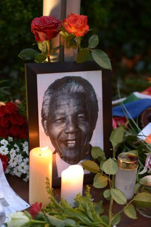Flowers and a photo of former South African President Nelson Mandela are placed in front of the South African embassy in Berlin, Germany in tribute to Mandela, who died Dec. 5 at age 95. (AP Photo/dpa, Rainer Jensen)