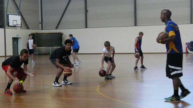 HANDS-ON: Coach Jay Washington leads the junior basketballers through dribbling skills at Raymond Laurie Sports Centre in Yamba. PHOTO: CONTRIBUTED