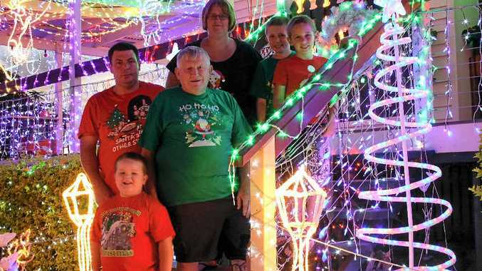 Geoff Beattie has covered his home in thousands of Christmas lights to bring joy to others in the community. Geoff Beattie (centre) with Chris Hollier, Fionna Hollier, Brock Hollier, James Beattie and Joshua Hollier.