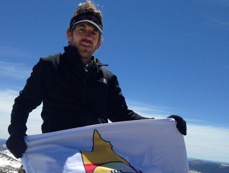 Gavin Bendall celebrates with the CQ NRL Bid flag at Australia's highest point after reaching the top of Mount Kosciuszko during the 2013 Coast to Kosciuszko Ultra Marathon.