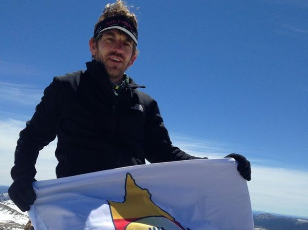 Gavin Bendall celebrates with the CQ NRL Bid flag at Australia's highest point after reaching the top of Mount Kosciuszko during the 2013 Coast to Kosciuszko Ultra Marathon.