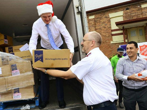 GIVING BACK: Ipswich Mayor Paul Pisasale and Steggles' Charles Rapa (right) hand out frozen turkeys to Greg Pack (centre) from the Salvation Army.