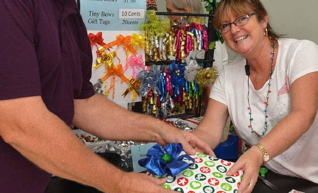 Volunteer Gail Sharpe helps Wayne Klarenbeck to wrap Christmas presents at Caneland Central.