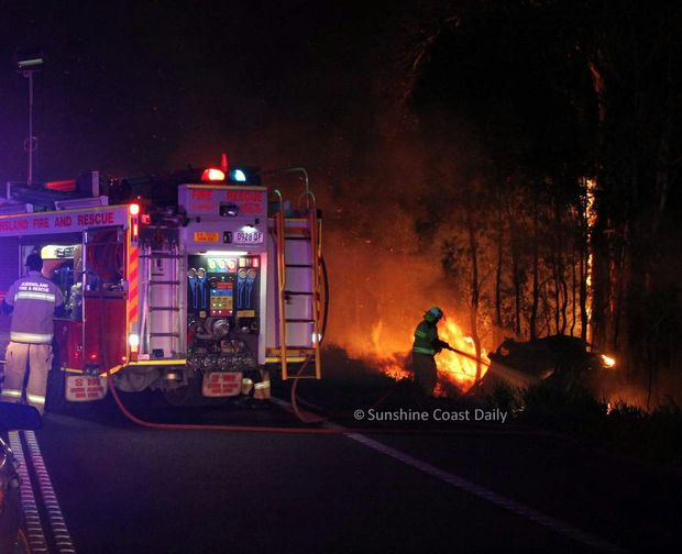 Firefighters extinguish a car fire following a head on collision on Sunshine Mwy at Coolum.
