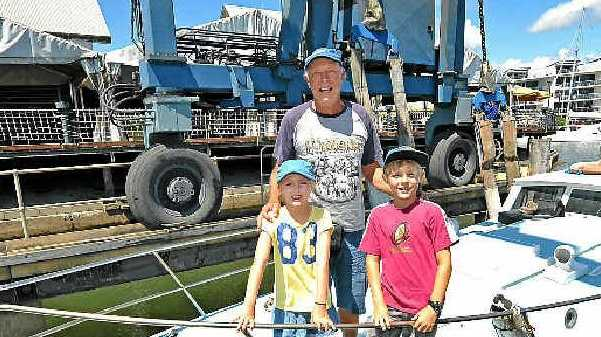 VESSEL WITH HISTORY: Neil Odger's labour of love, his boat, Sandfly, moored in Kawana. Aboard are Greg Seghit with his grandchildren Troy and Ellie Milton.