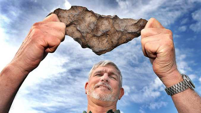 Russell Wardrope of the Hervey Bay Gem and Mineral Club with a piece of iron meteorite found in the Northern Territory at the Hemburg Craters.