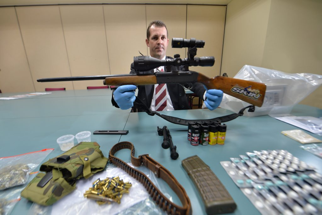 Detective Senior Sergeant Luke Peachy with a semi-automatic weapon found among other items and drugs seized during two separate raids in August.