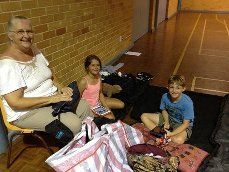 Holiday-makers Chris Schindler of Tasmania with her grandsons Eilli and William Fearn of Bowen, Queensland, at the bushfire evacuation centre at Byron High.