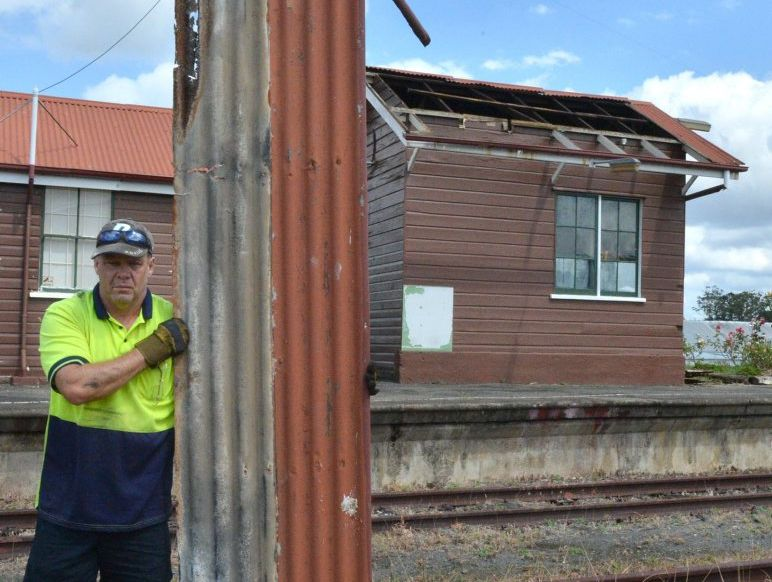 Tony Hallem collects roofing iron that was torn from one of the buildings at the old Gympie station when Friday nights storm passed through.