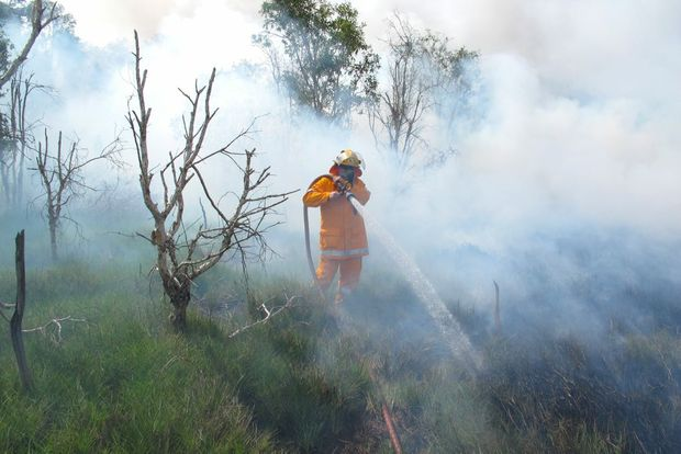 A member of The Caves Rural Fire Brigade helps to control the fire at Sandy Point in January this year.