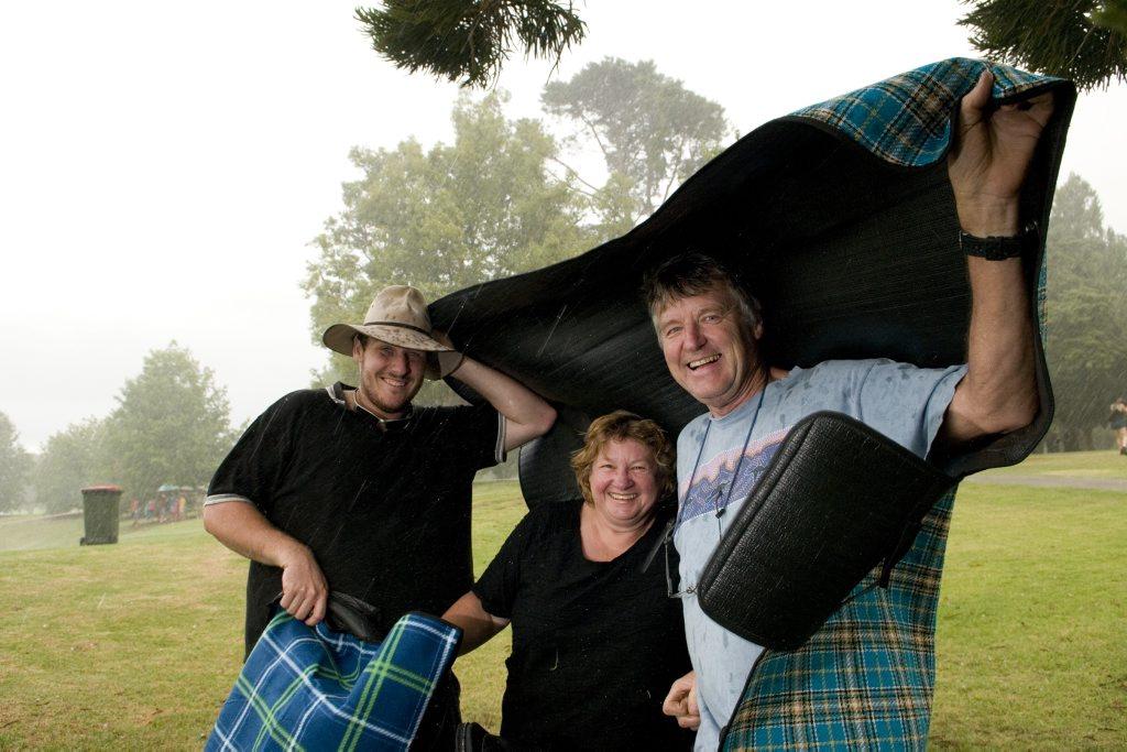 (From left) Hugh Kingdom, Liz Boardman and Bruce Boardman shelter under their picnic rug from the rain and hail at the New Year's Eve Fireworks and Family Fun Evening at Queen's Park, Tuesday, December 31, 2013. Photo Kevin Farmer / The Chronicle