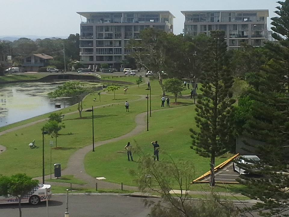 A man holding a knife to his chest at Nelson Park.