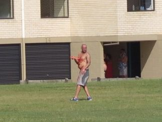 A man holds a knife to his chest at Nelson Park, Alexandra Headland.