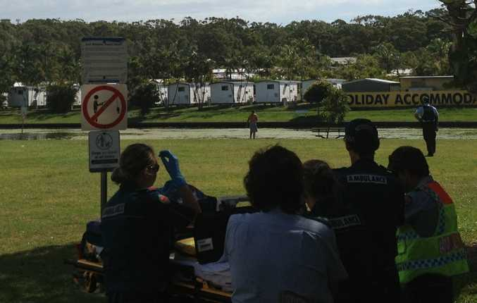 Police talk to a man at Nelson Park, Alexandra Headland.