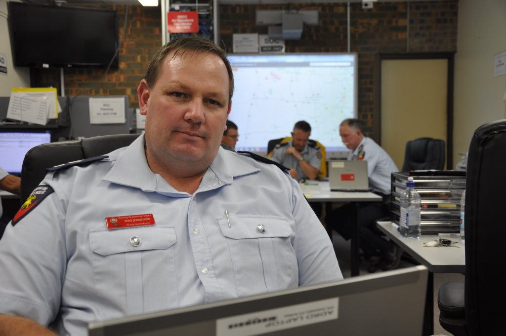 Rural Fire Service Queensland officer Acting Superintendent Tony Johnstone monitors fires with his colleagues at the Anzac Ave Regional Operations Coordination Centre.
