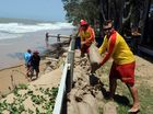 Lifesavers Thomas George (front) and Connor Murray stack sandbags as strong winds and a king tide combined to erode Torquay beach on Saturday.