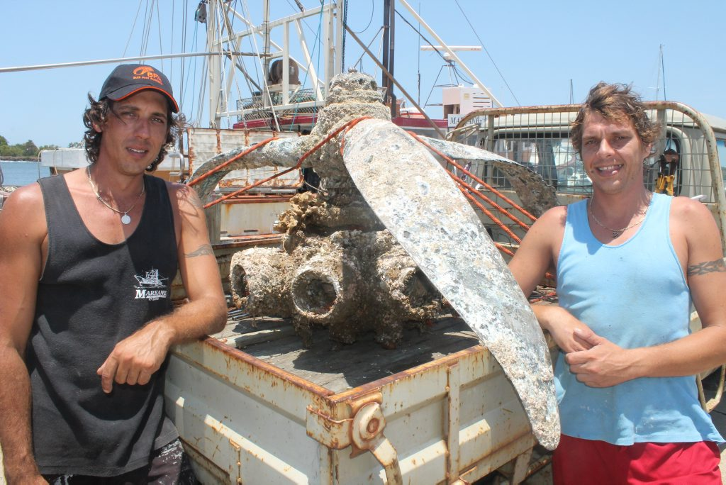 UNUSUAL CATCH: Ballina trawlermen Brendan Puglisi (left) and Shaun Cameron with what is believed to be a WWII vintage aircraft engine they pulled up from the ocean floor last Thursday night. Photo Graham Broadhead / Ballina Shire Advocate