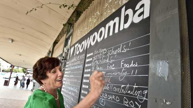 Cr Carol Taylor writes on the I Love Toowoomba blackboards in Margaret St.