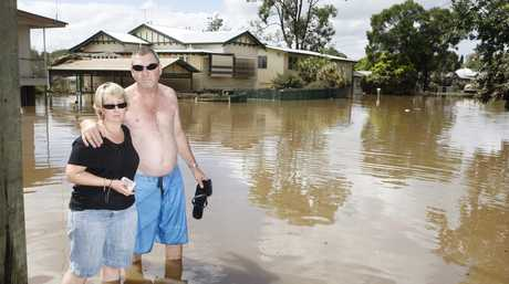 The Grams in front of their home in the wake of the 2011 floods.