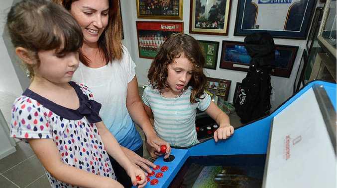 Tessa, 5, Cadence, 8, and mum Katrina Pirie give some old arcade games a go.