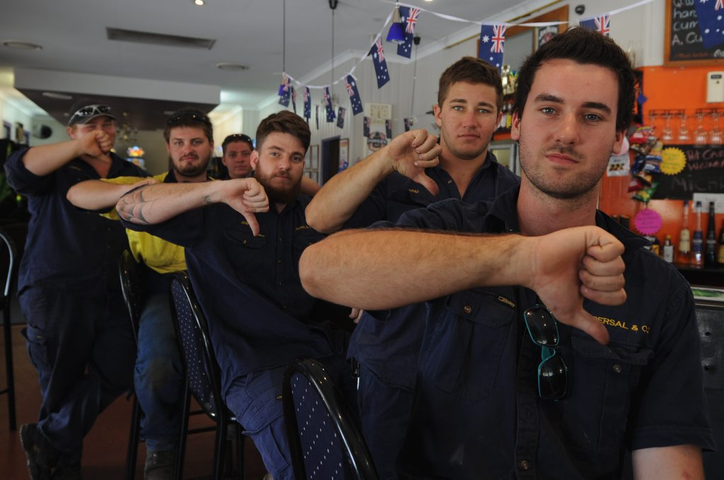 Nick Grieves and workmates give a big thumbs down to the person who stole the Australian flag from the Lamington Hotel.