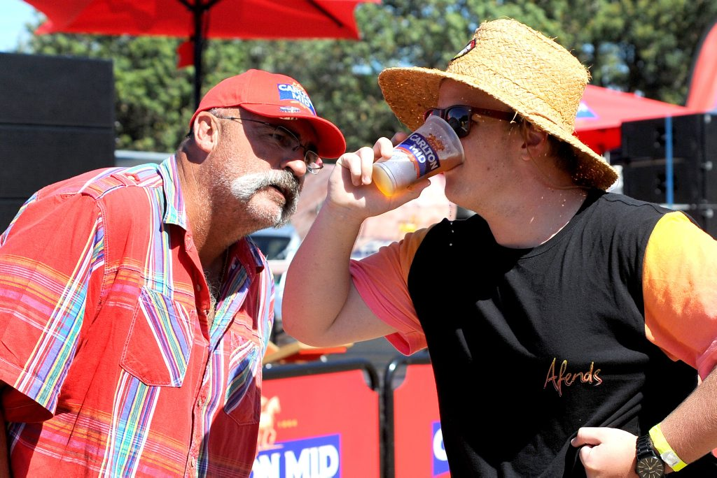Merv Hughes watches Liam Gavin scull his beer at the ODI cricket on the big screen at Park Beach reserve. Photo: Leigh Jensen/ The Coffs Coast Advocate