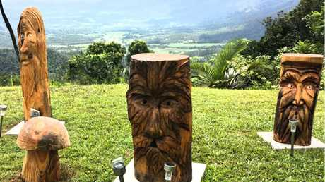 GREEN MEN: Wood sculptures which now stand watch over the Pioneer Valley at the front of the Eungella Chalet are the work of Finch Hatton man Neil Brooks.