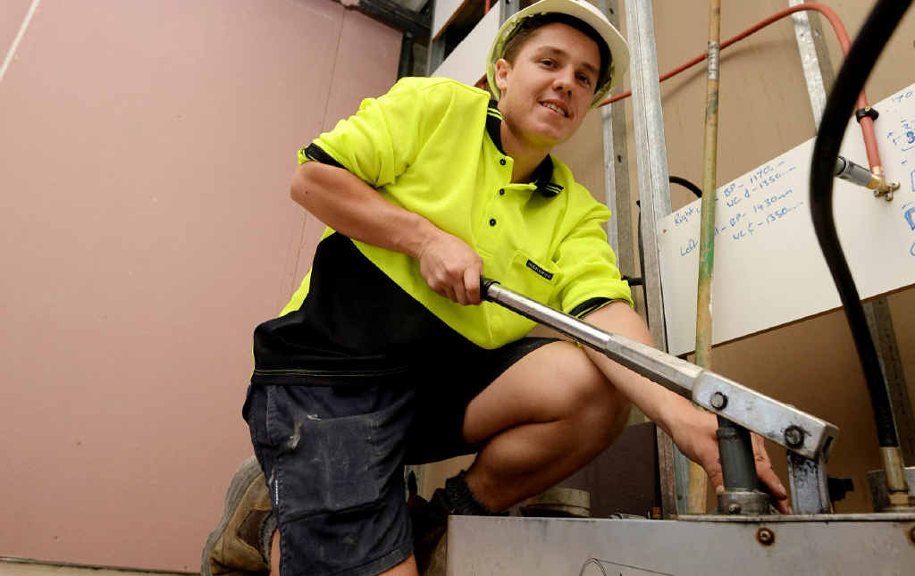 ON THE JOB: JM Kelly Group apprentice plumber Tim Zimitat at work on The Empire building on Victoria Parade.