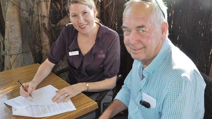 Capricorn Enterprise CEO Mary Carroll signing the MOU with Capricorn Business and Tourism President Brian Fisher. Photo Trish Bowman / Capricorn Coast Mirror