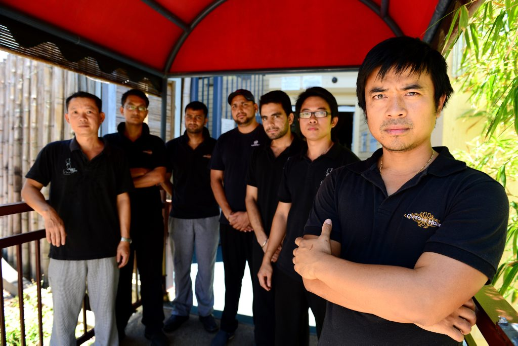 Saigon Saigon owner Tai Lam (far right) with staff members Hua, Ryan, Mahesh, Vishal Gaur, Harry and Steven. People have been throwing rocks at customers in their restaurant. Photo Sharyn O'Neill / The Morning Bulletin
