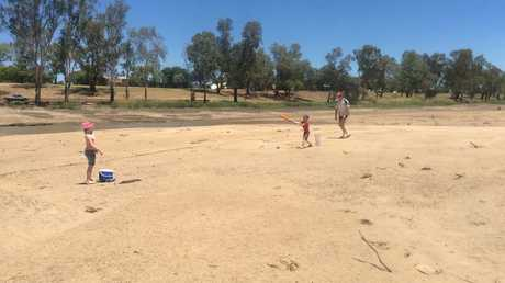 The Ferguson family plays a game of cricket on the dry Balonne River.