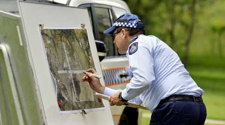 Sergeant Paul Andrews checks the map where the SES and police are conducting searches for missing woman Constance Cafarella. Photo: Claudia Baxter / The Queensland Times