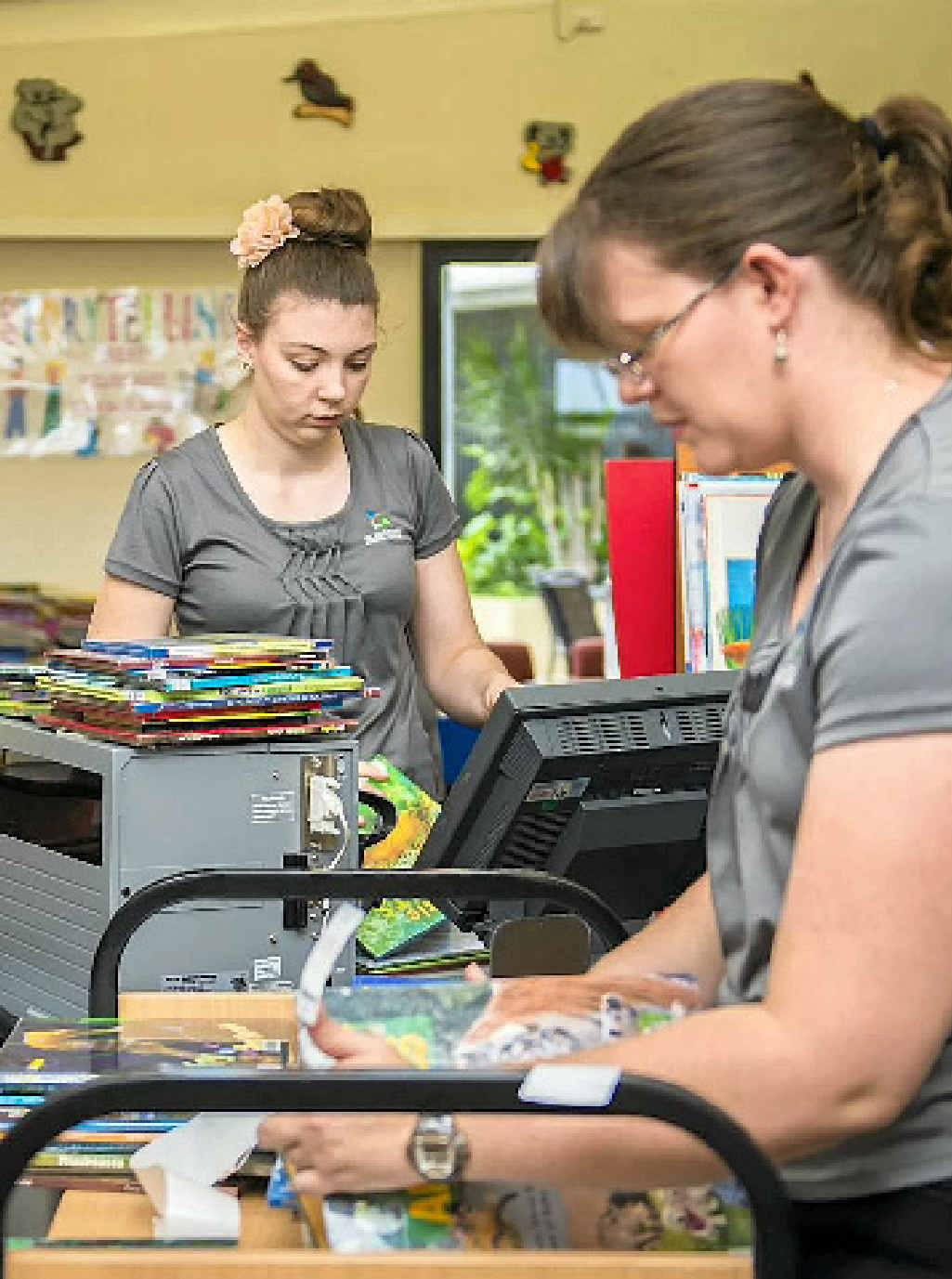 BOOK WORMS: Library assistants Janie Steeo and Natalie Hinde tag books to get ready for the self-service book borrowing.