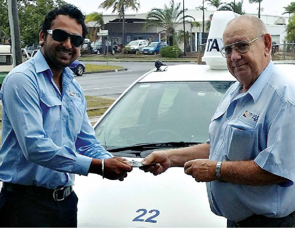 PAYBACK: Amrik Singh Sidhu hands over a sum of money he found in the back seat of his vehicle to Blue and White Taxis' Allan Rowe.