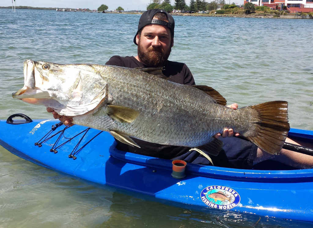 HOOKED ON LIFE: Matt Gibbs and the big barra he reeled in from his little canoe.