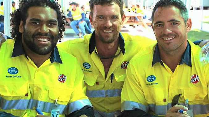 League fan Ewan Hetherington with Brisbane Broncos players Sam Thaiday (left) and Corey Parker at the GLNG site on Curtis Island.