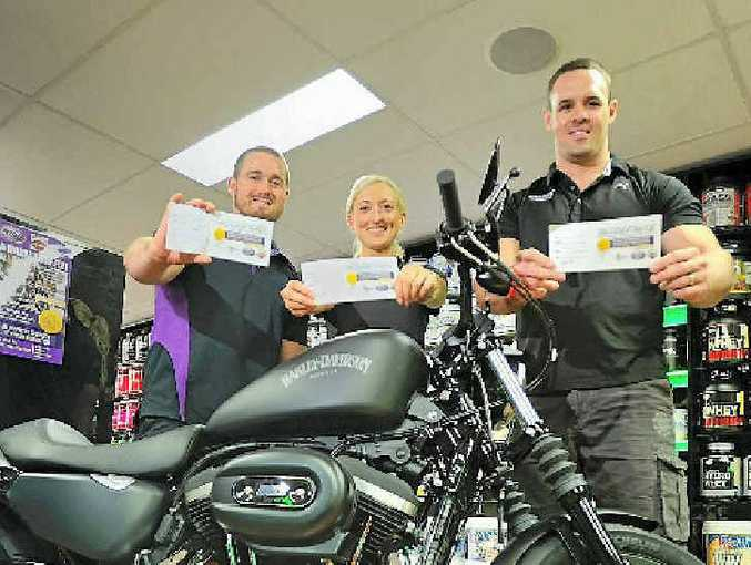 WIN A BIKE: Australian Sports Nutrition is selling tickets for a charity, and people who buy the tickets go into the draw to win a 2014 Harley-Davidson 883 Sportster Iron. Pictured are Joel Ibbotson, Whitney Sreyling and Ben Murphy.