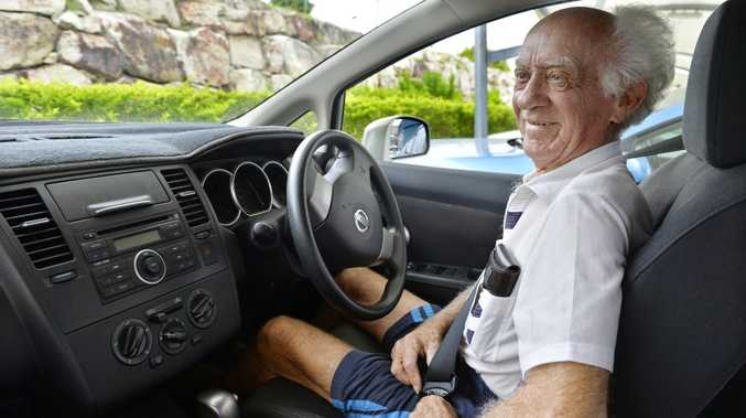 83-year-old driver Graham Kelly concentrates behind the wheel, and is happy to have annual medical checks to maintain his driver's licence.