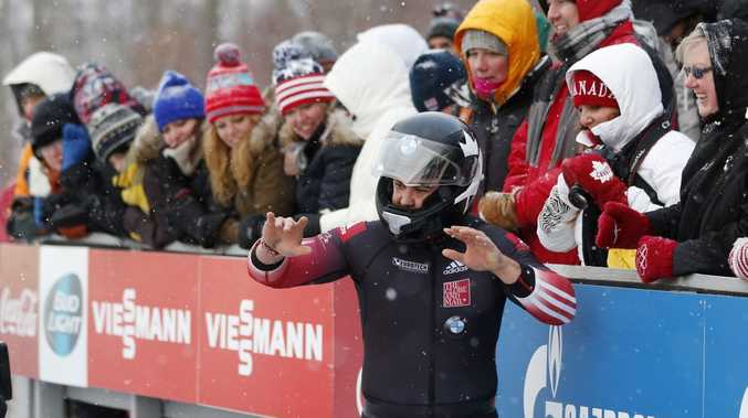 Canada's pilot Chris Spring celebrates with fans after his team's fourth-place finish in the four-man bobsled World Cup event on Sunday, Dec. 15, 2013, in Lake Placid, N.Y. (AP Photo/Mike Groll)