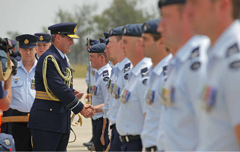 COUNTRY'S HONOUR: Chief of Air Force, Air Marshal Geoff Brown, presents combat badges to members of the Multi-National Base Command - Tarin Kot and Security Force at the welcome home parade.