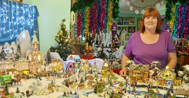SOURCE OF JOY: Carol Cross stands with the Christmas village she assembles each year.