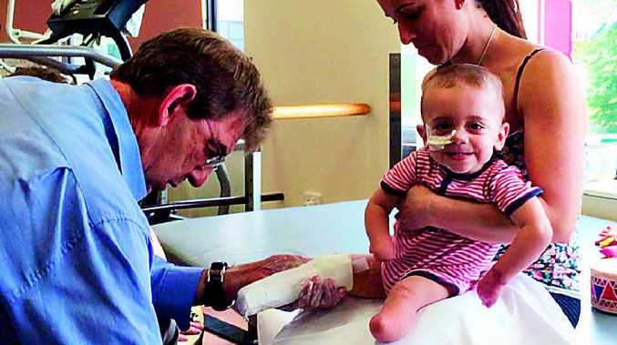 """Tiny tot Finn Smith still manages a smile as he gets his new """"legs"""" sized up yesterday."""