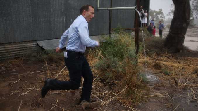 Prime Minister Tony Abbott dashes through a downpour as he meets graziers and community members at the shearing shed of Phillip and Di Ridge of