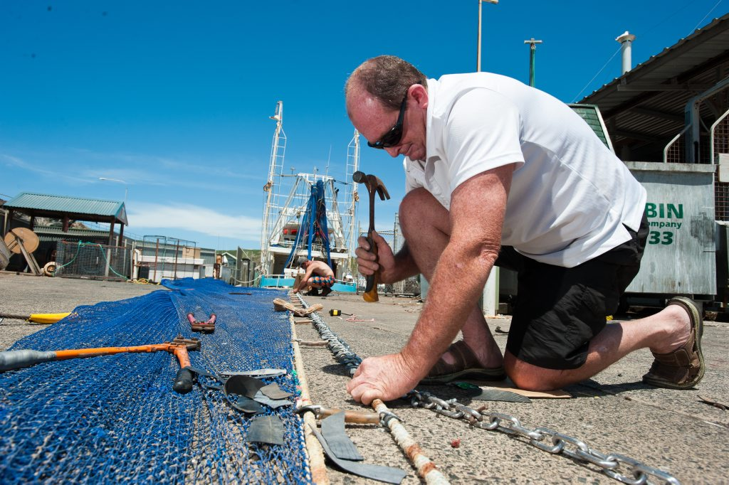Fisherman Phil Ward repairing fishing nets at Coffs harbour Interntional Marina. Photo: Rob Wright / The Coffs Coast Advocate